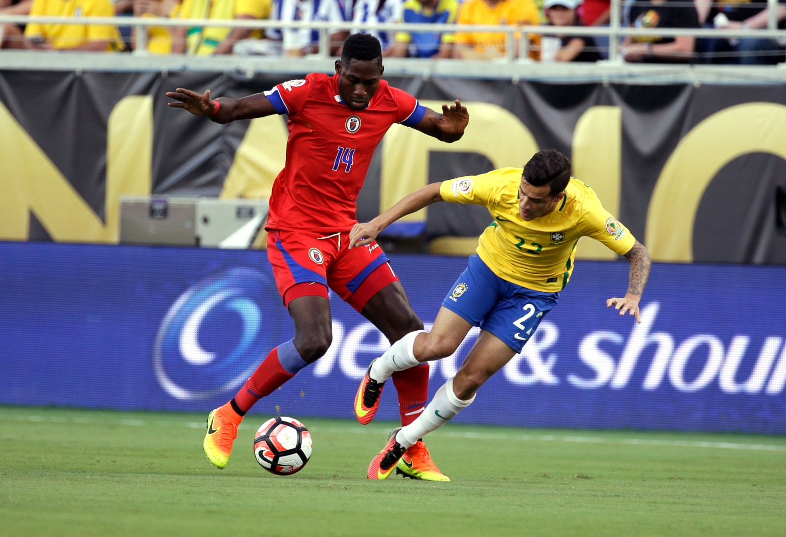 Haiti's James Marcelin (14) and Brazil's Philippe Coutinho (22) collide while going for the ball during the first half of a Copa America group B soccer match at Camping World Stadium, Wednesday, June 8, 2016, in Orlando, Fla. (AP Photo/John Raoux)