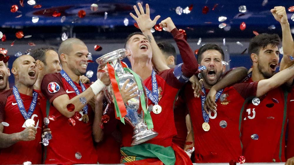 Pepe pega a taça das mãos do capitão Cristiano Ronaldo (Foto: AP)