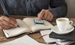 Hand of man writing something in blank notebook on wooden office table. Closeup. Copy space. Free space for text