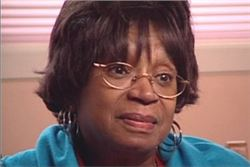 Lois, Survivor: older African American woman wearing glasses, teal blouse