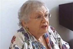Anne, Survivor: older woman wearing eyeglasses, with short gray hair and a floral blouse