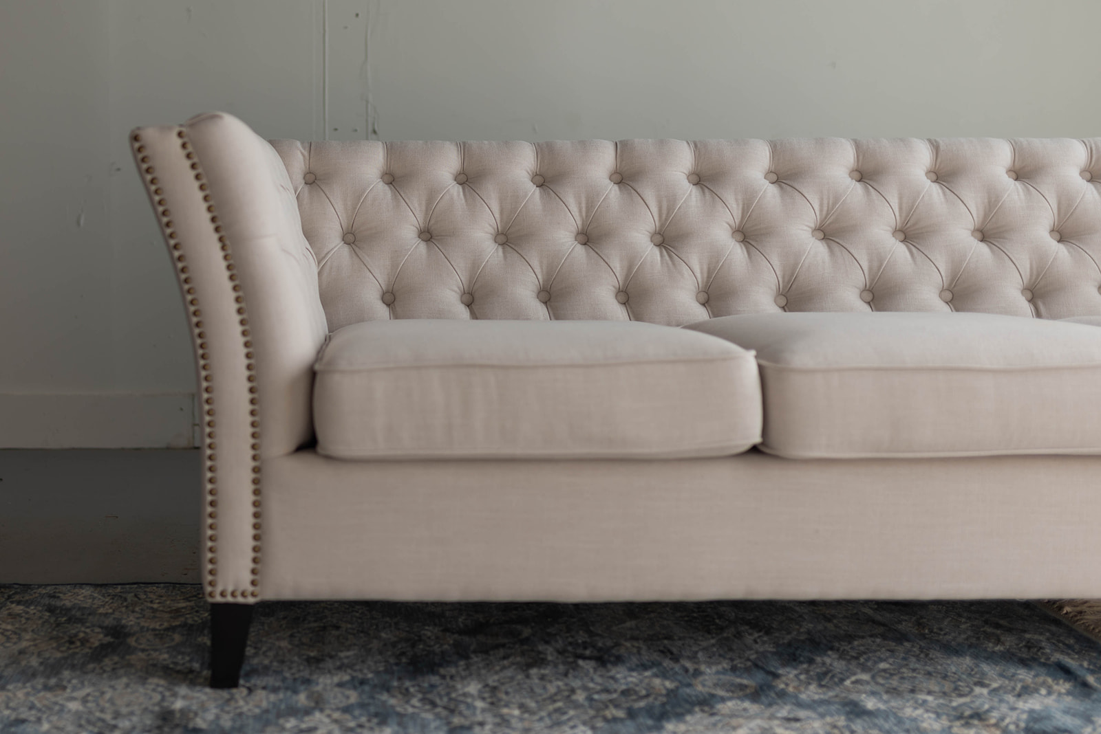 Linen tufted sofa with nail heads
