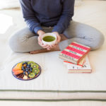 Girl sitting on an organic mattress with books, a cup of green tea, and a colorful plate of assorted fruits.