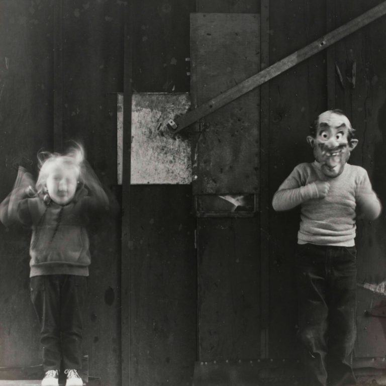 Black and white photo by Ralph Eugene featuring two children standing in haunting poses. A little girl stands with her arms raised with blurry face and hands to indicate motion. An older boy stands to the right of her wearing a mask. The mask is of a balding old man with mustache and a goofy expression. The backdrop is