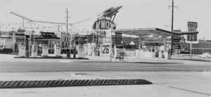 "Black and white photograph depicting a roadside gas station. There are several 60s-era gas pumps on a concrete island, and four signs saying various combinations of ""Stop,"" ""Save"", and ""26.9."" There is a large oval sign in the middle of the photograph with the word ""Knox"" shown in capital letters. Mounted at the top of the sign is a 50s depiction of a rocketship, with three bullet-shaped rockets."