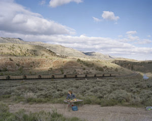 A small child is playing with multi-colored trains on a folding card table on a gravel road. There is a plastic bin in front of the table. The table and the child sit on a gravel clearing in the middle of a mountain landscape, with low shrubs around. The child is looking over her right shoulder at a passing freight train. Visible in the photo are 11 identical brown freight cars. The train travels on one of two parallel tracks, which wrap around one of the mountain draws and out of sight. The sky is blue, with about 50% cloud cover.