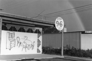 """A concrete overhang with a prominent circular sign advertising """"Open 9 to 6, Closed Sun"""" is attached to the right side of the overhang. Under the overhang is a large drawing of a table and chairs set, as well as a china hutch. The drawing is surrounded by graphic blocks. In the background, a rainbow is visible through several power lines."""