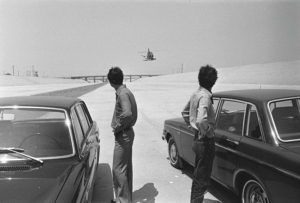 Black-and-white image depicting two cars, two men facing away from the camera, and a helicopter in the distance framed between the two men. A shallow river is visible on the left. The remainder of the landscape is concrete. A bridge is visible in the distance.