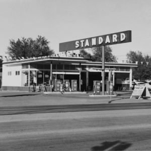 "A road crosses in front of the camera in the foreground. Across the road is a gas station, with a large sign with the word ""STANDARD"" mounted above it. There are two concrete islands, one with two gas pumps and one with three. There is a garage attached to the station, with three open bays. Signs for tires and tune-ups litter the area."