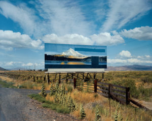 Color image of a billboard to the right side of a road. The billboard is a painting of a snow-capped mountain, and mirrors the colors of the sky behind the billboard. The billboard is standing amidst low bushes and grasses, and intersects with a wooden fence running alongside the road. In the distance, a mountain range is visible.