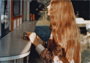 A younger woman with long red hair is in the foreground, facing to the left. She is holding money in her right hand, and both of her hands are on a counter. She appears to be standing outside at a window preparing to order food.