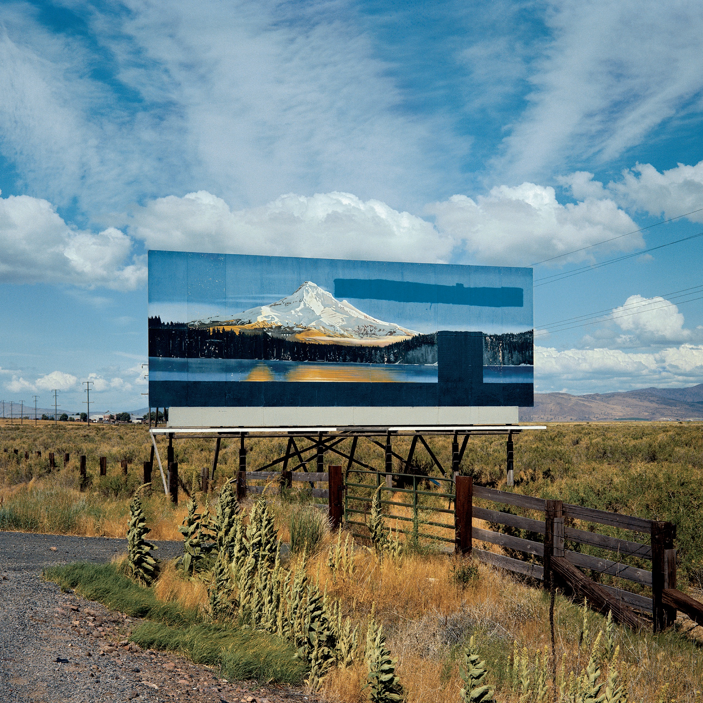 Image of a billboard by a roadside. The billboard depicts an image of a mountain in the distance with clouds. The color of the billboard mirrors that of the sky and clouds behind the billboard. There is a brown fence running along the side of the road, with weeds, grasses, and shrubs coming right up the the edge of the gravel road, which is seen in the lower left-hand corner of the image.