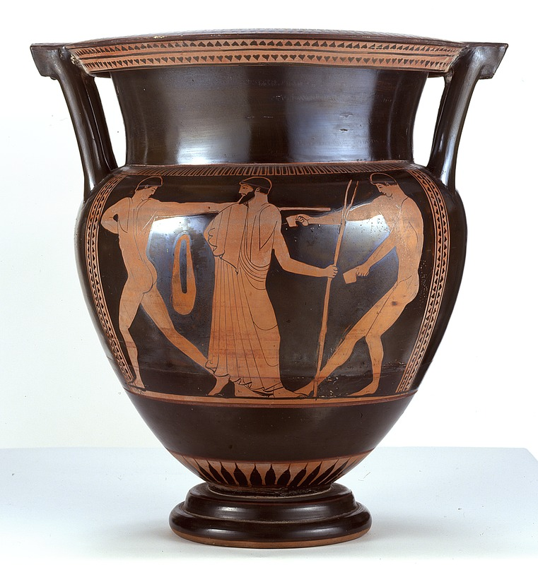 Image depicts a black two-handled vase with three orange figures.