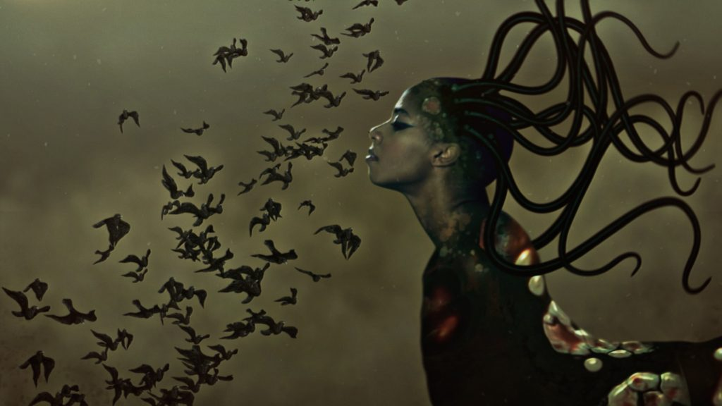 Wangechi Mutu, The End of eating Everything (video still). Strange figure with a womans face and flowing snake like hair, in front of her are a swarm of birds
