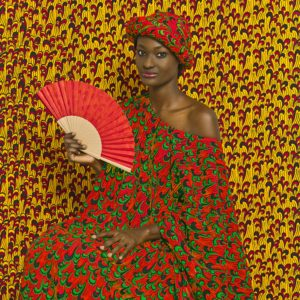 Photograph from the series The Studio of Vanities featuring a person holding a fan in brightly colored dress with patterns that repeat on the background