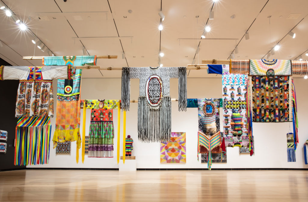 Installation view of colorful garments hanging from the ceiling shown in the exhibition Jeffrey Gibson: This is the Day