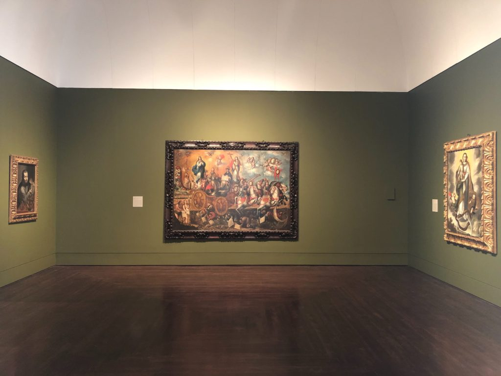 A gallery view inside Art of the Spanish Americas, In the Middle of the room is one large painting El Triunfo de la Inmaculada