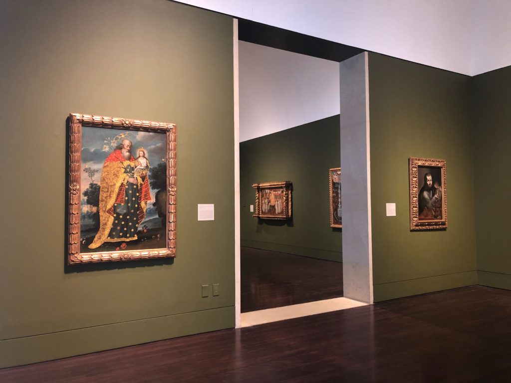 A photo in the galleries of Art of the Spanish Americas, on either side of the doorway you can see two paintings. The one on the left side is a painting of San Joaquín y la Virgen María niña, On the other side of the door two more paintings are visible but not distinguishable from such a far distance