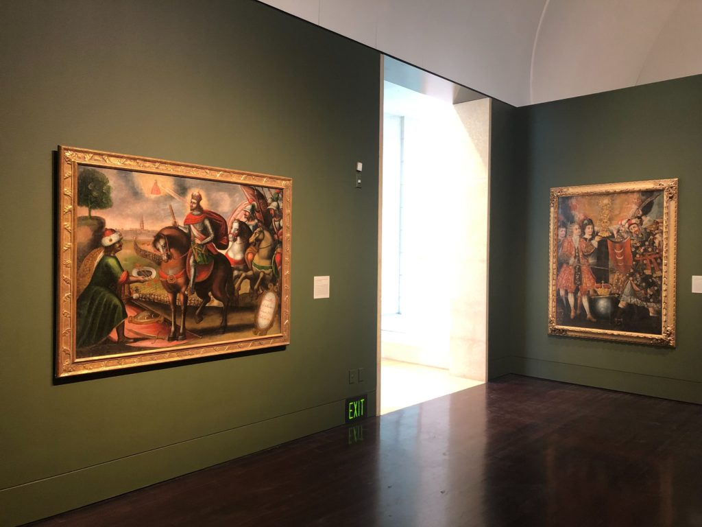 Photo inside the galleries of Art of the Spanish Americas, with two painting s visible The Surrender of Seville to Saint Ferdinand III, by Unknown, on the left side and the, Defense of the Eucharist by Philip V of Spain, by Unknown on the right hand side