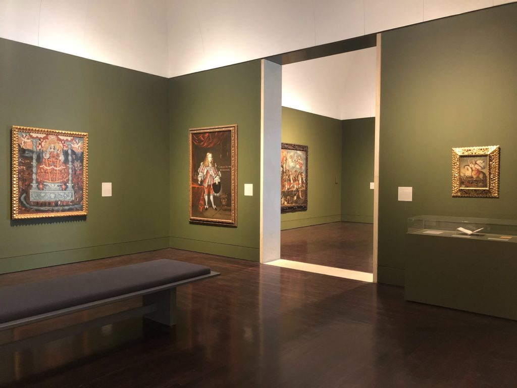 View of two Spanish Americas galleries. Walls are painted army green which the paintings stand out against in their gold guilded frames.