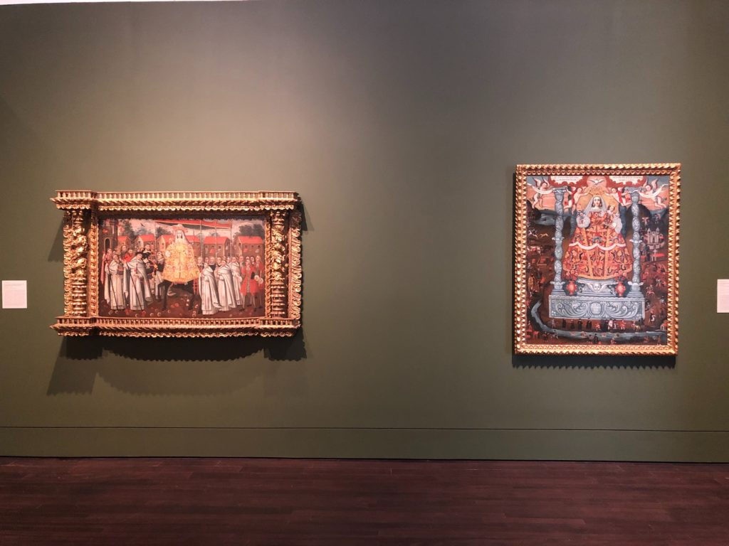 Two large scale paintings of female saints hung next to each other in elaborate gold guilded frames. Each painting depicts the lady in ornately embroidered clothing surrounded by onlookers.