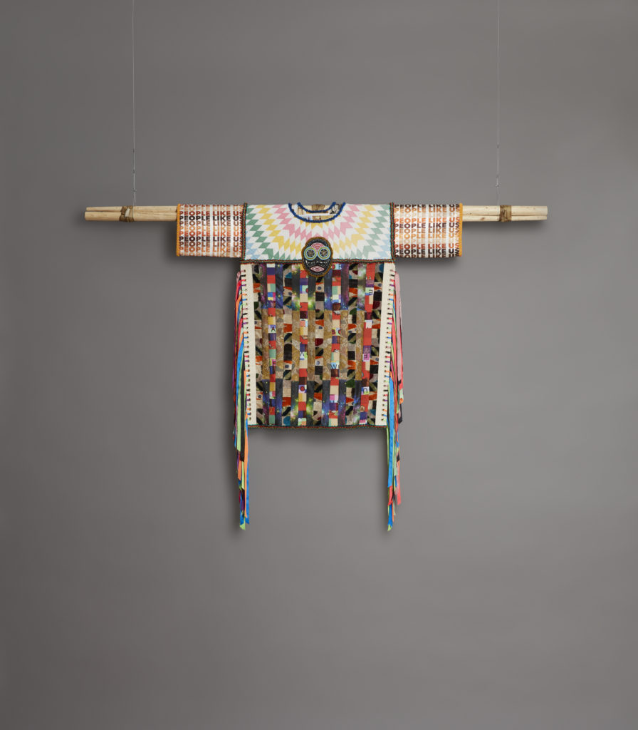 "An elaborate patchwork costume, with ""People Like Us"" printed on it, is hung from the ceiling"