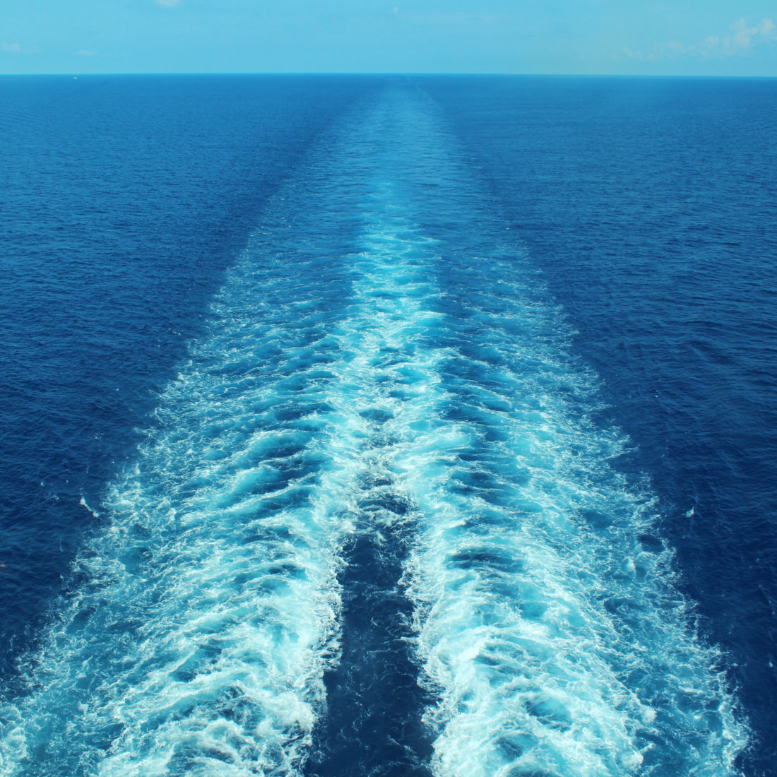 Image of the sea with trails on the surface left by a boat.