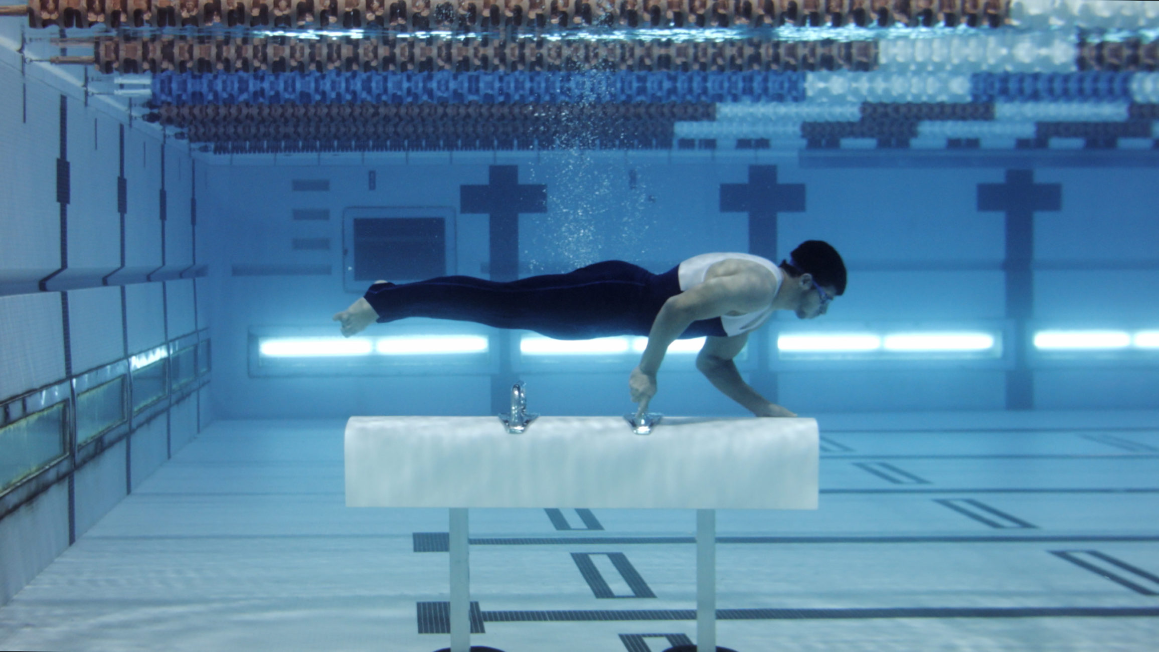 Video still of man underwater in a swimming pool