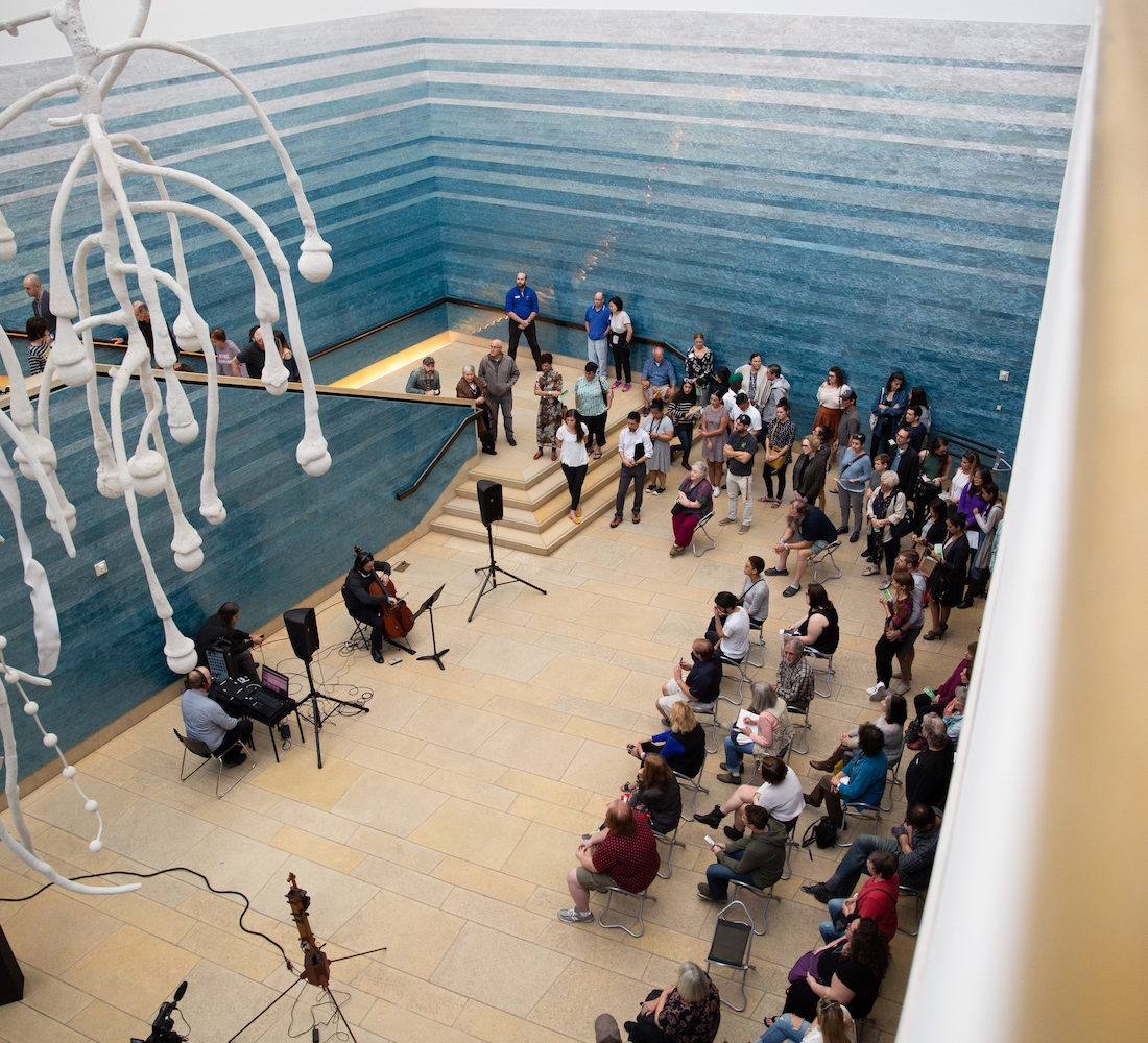 A photo taken from the mezzanine of the Blanton Museum of Art, looking down at the atrium which is filled with an audience watching a musical performance.