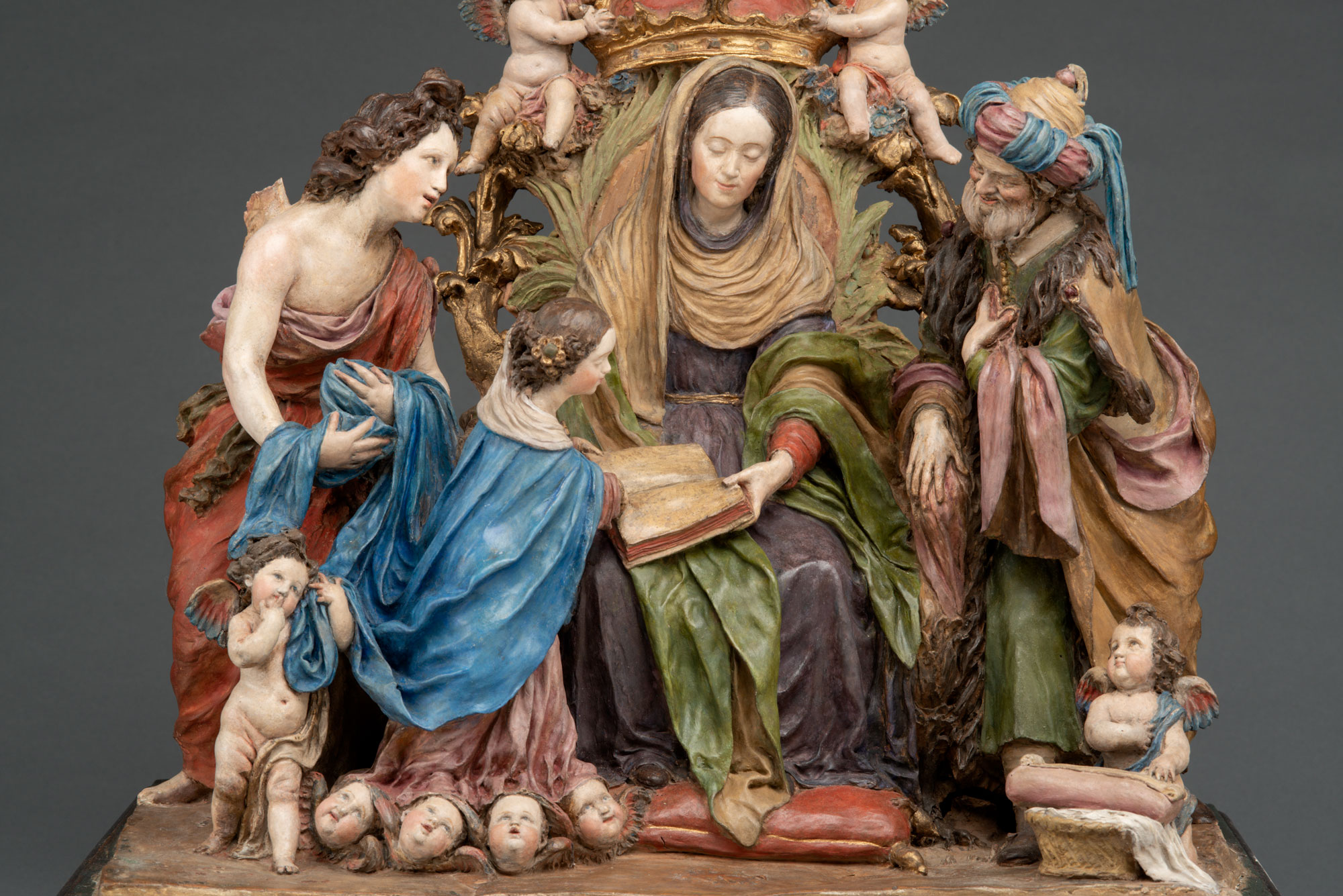A small painted sculpture of a family encircling a woman. She shares a book with them, while cherubs and winged baby heads look on