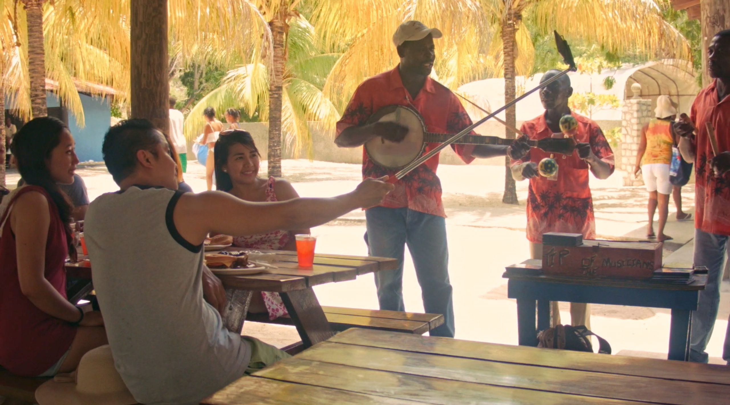 "Joiri Minaya, ""Labadee"" (still) featuring a group of tourist eating taking photographs in front of a local street musician, 2017, HD video, 7 min 10 sec, Image courtesy of the artist."