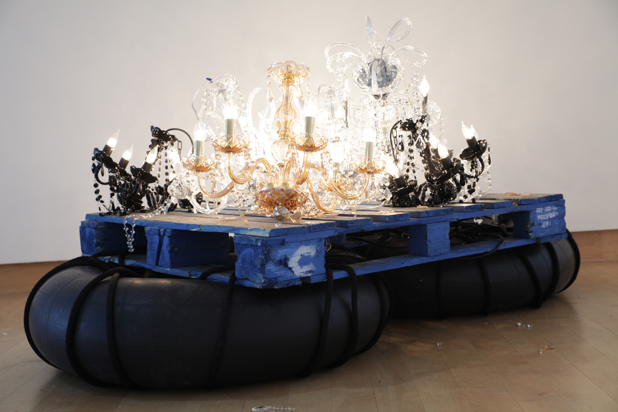 """""""Fathom"""" by Kambui Olujimi, installation with six chandeliers, rubber inner tubes, and wooden pallets"""