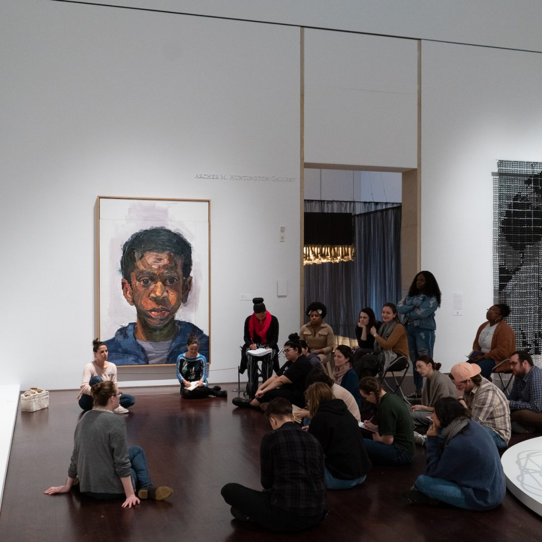 "A class group sits in a semi circle to discuss the work ""Parade (diptych)"" by Mequitta Ahuja in the modern and contemporary gallery"