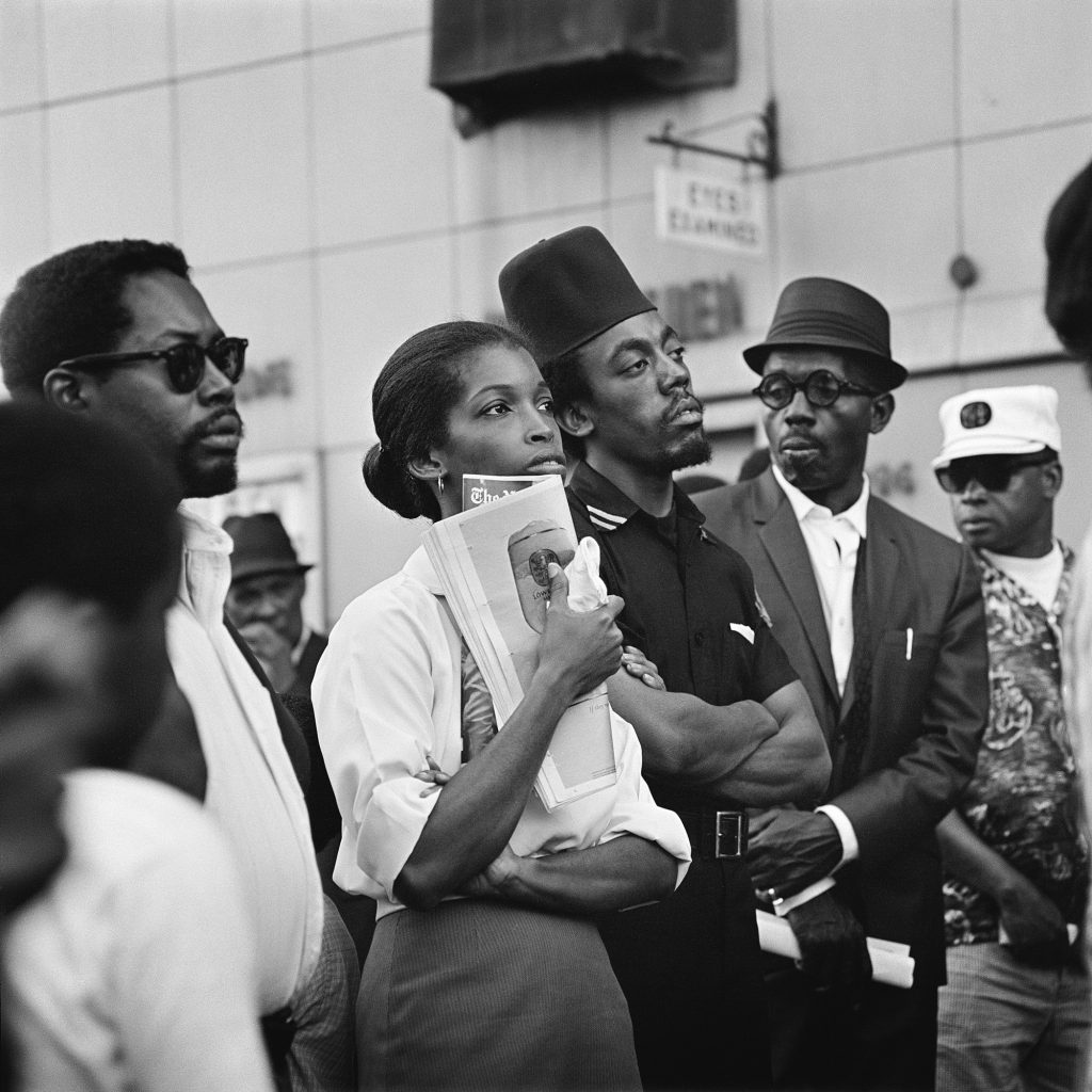 Photo of a group of people looking up at Marcus Garvey Day Parade, Harlem, circa 1967; from Kwame Brathwaite: Black Is Beautiful(Aperture, 2019), Courtesy the artist and Philip Martin Gallery, Los Angeles