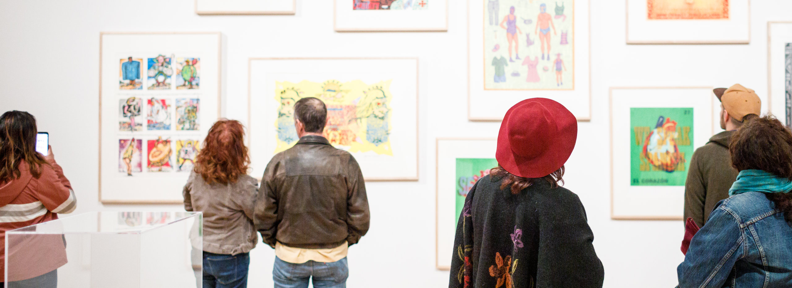 """A selection of people looking up at a wall featured in exhibition """"Words/Matter: Latin American Art and Language at the Blanton"""""""