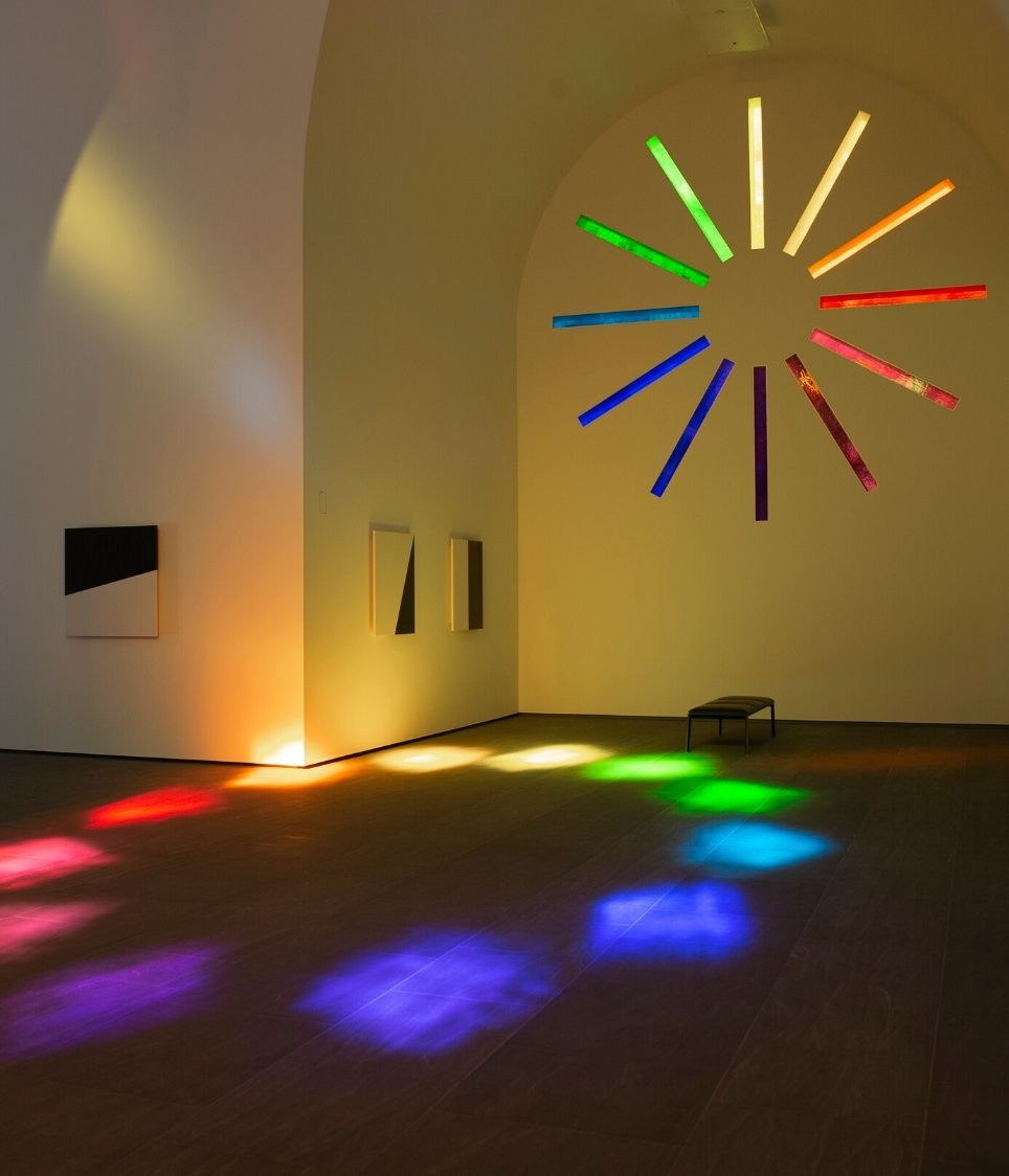 """View inside """"Austin"""" building by Ellsworth Kelly, with light reflections on the interior from the colored glass windows."""