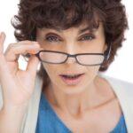 Cirurgia Refrativa: foto de mulher abaixando os óculos de grau para a ponta do nariz tentando enxergar com dificuldade algo que está a sua frente