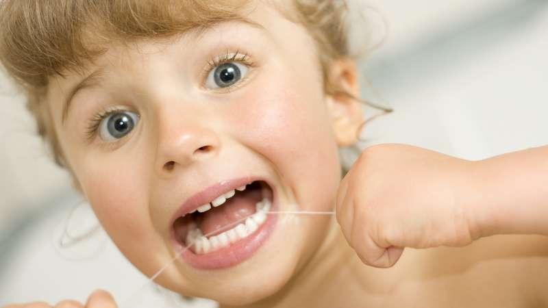 Criança limpando os dentes com o fil dental