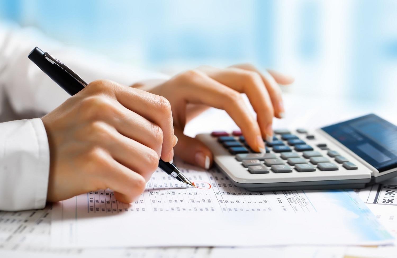 Mãos femininas usando uma calculadora e uma caneta.