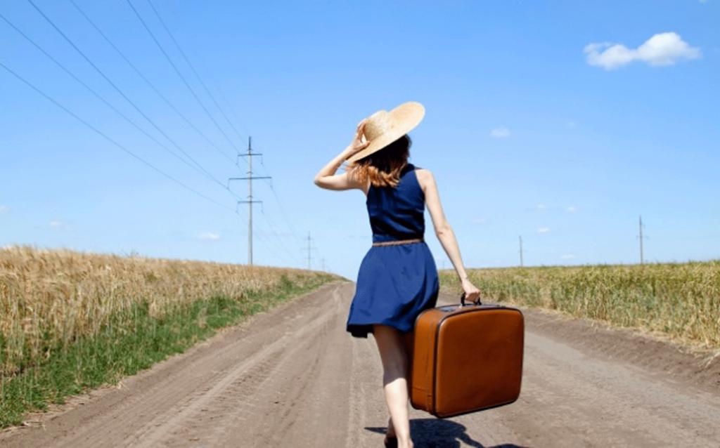 mulher de costas segurando uma mala na estrada