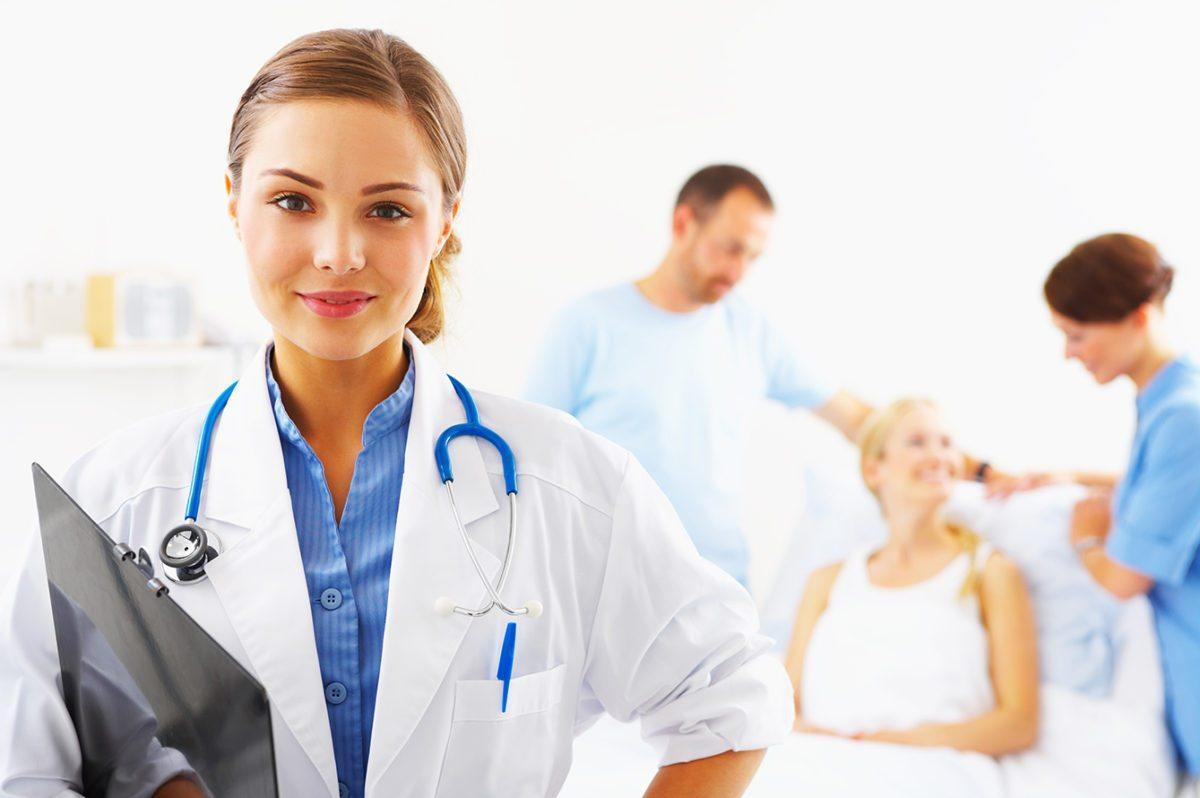 mulher com jaleco branco, estetoscópio no pescoço, meio sorriso, mão na cintura e prancheta no outro braço
