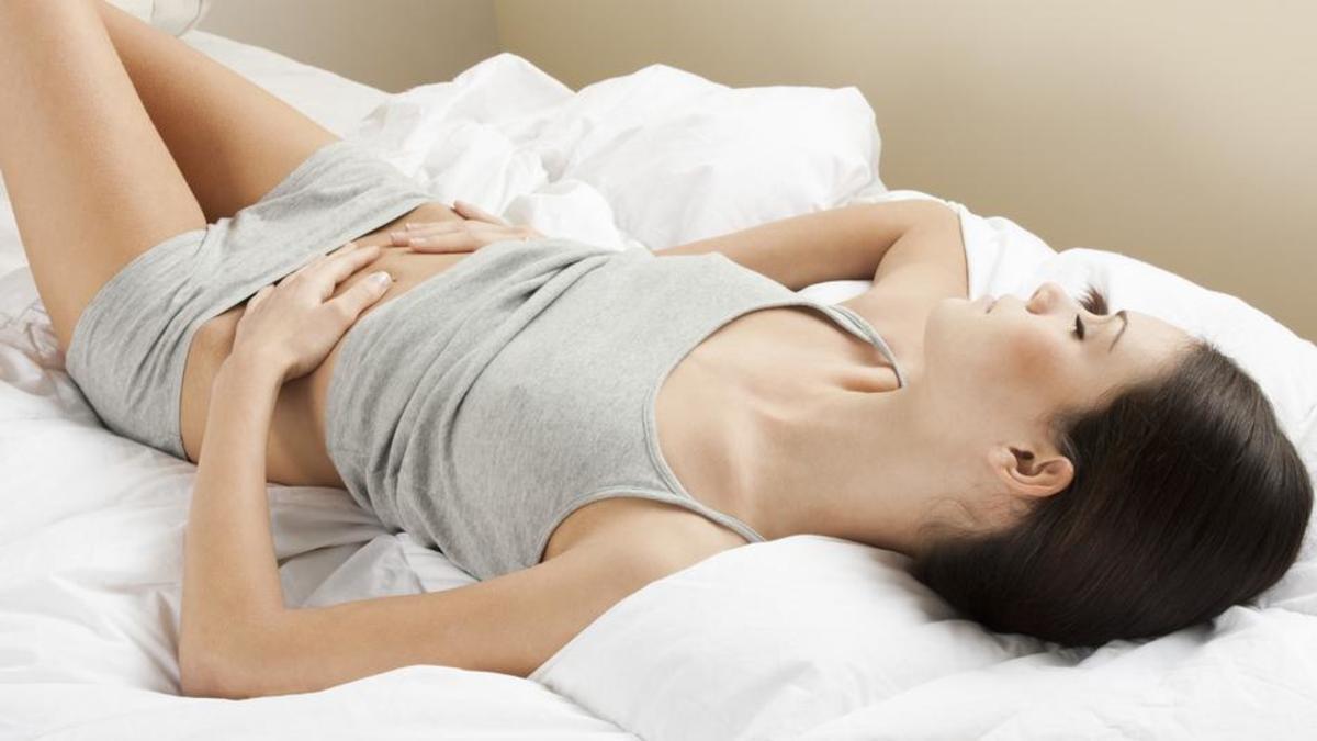 mulher deitada com as mãos em cima da barriga