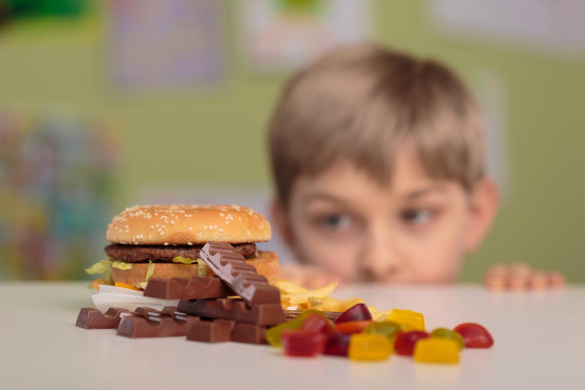 menino olhando para lanches e comidas calóricas
