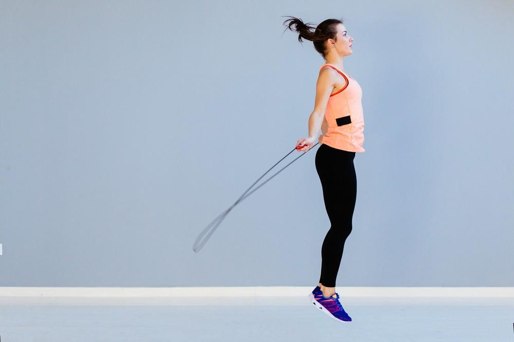 mulher em fundo azul pulando corda praticando exercicio