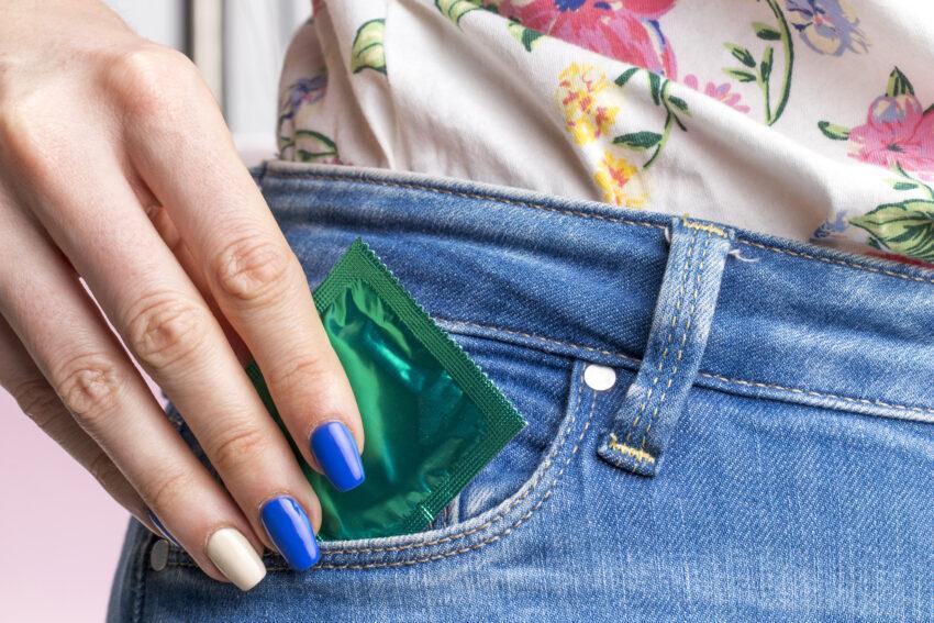 cuidados com saúde: Imagem de bolsa de calça de mulher e preservativo no bolso