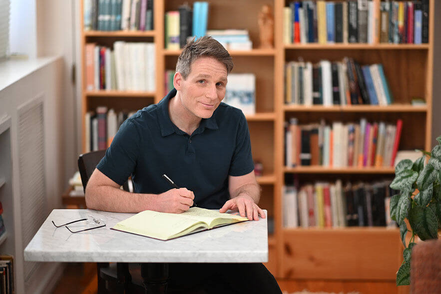 Soken writing in front of book shelf