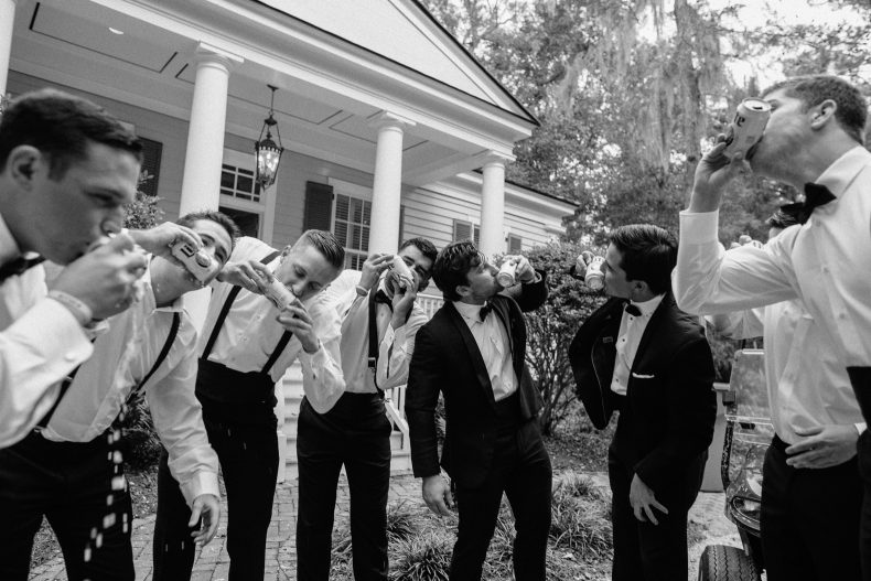 groom and groomsmen shotgunning a beer morning of the wedding