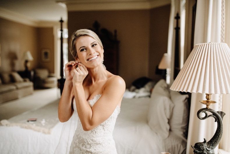 blonde bride in lace fitted wedding gown putting in earrings
