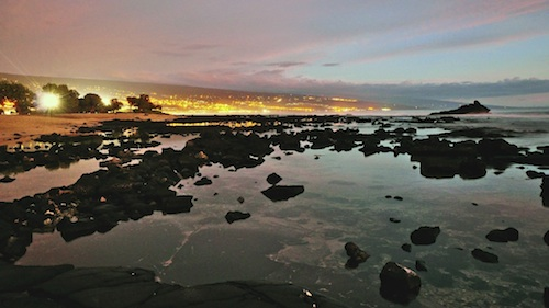 Kailua-Kona after sunset, with volcanic rocks on the beach in the foreground. Courtesy of Steve Dunleavy.