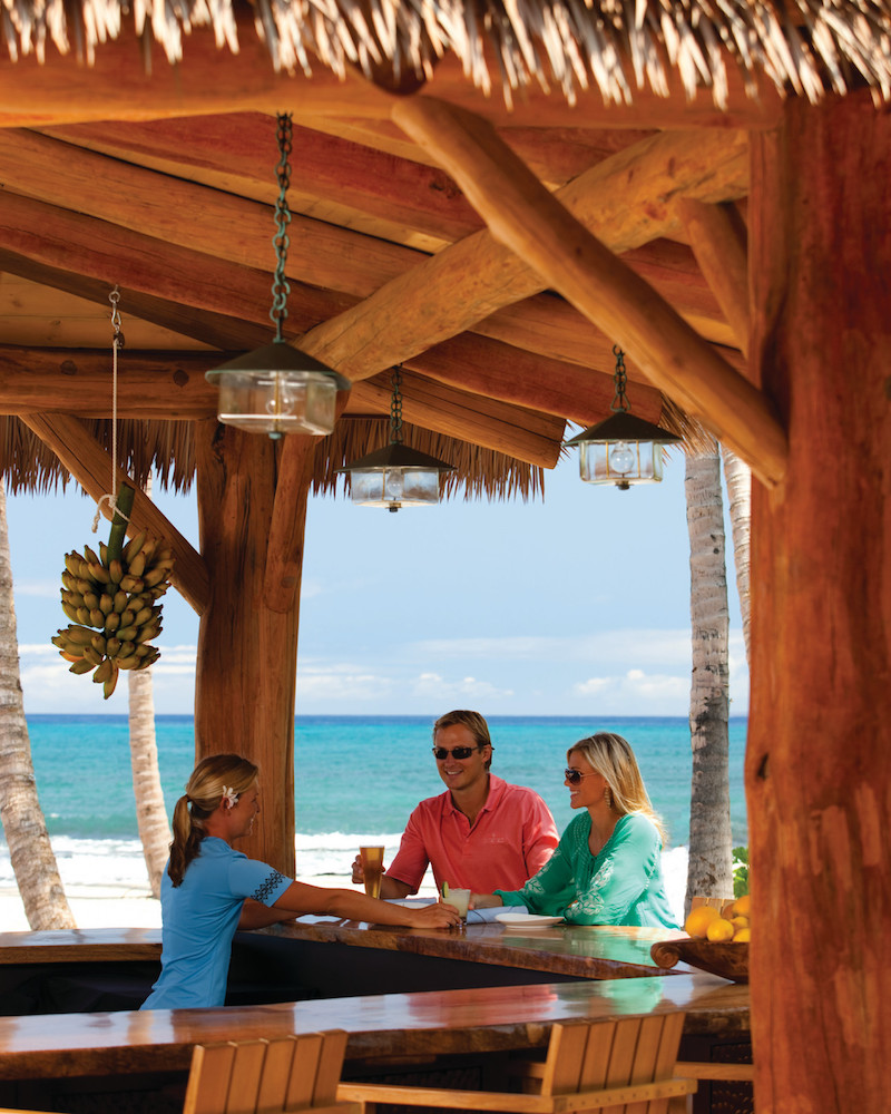 A couple drinking at the Beach Tree Bar and Lounge at the Four Seasons, arguably one of the best beach bars both on Hawaii and in the country.